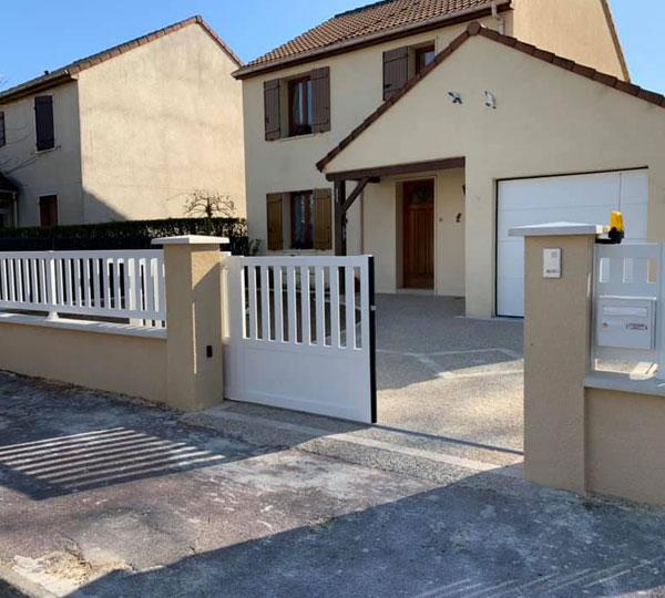 Installation d'un portail coulissant blanc et de sa clôture assortie
